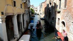 Gondoler med turister som fram och tillbaka seglar över den smala kanalen stock video