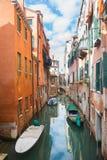 Gondoler som parkeras bredvid byggnader i vattenkanal Fotografering för Bildbyråer
