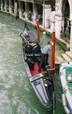 Gondolero en el barco ornamental en agua del canal foto de archivo