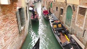 Gondolero veneciano en la góndola, turistas transportados a través de las aguas del canal de Venecia en Italia metrajes