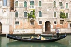 Gondolero veneciano que lleva en batea la góndola a través de las aguas verdes del canal de Venecia, Italia Foto de archivo libre de regalías