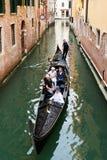 Gondolero veneciano que lleva en batea la góndola a través de las aguas verdes del canal de Venecia, Italia Imagenes de archivo