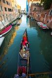 Gondolero veneciano que lleva en batea la góndola a través de las aguas verdes del canal de Venecia, Italia foto de archivo