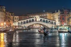 Gondolero y puente de Rialto en la noche Imagenes de archivo