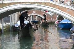 Gondoleros de Venecia que se acercan a un puente Imagen de archivo