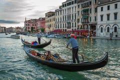 Gondoleros que navegan con los turistas en Grand Canal en la puesta del sol Imagen de archivo libre de regalías