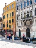 Gondoleros y turistas en la costa en Venecia imagen de archivo
