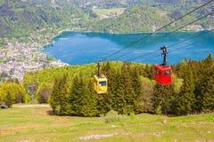 Gondoles de chemin de câble de Zwoelferhorn Seilbahn et d'une vue de ville alpine StGilgen et de lac Wolfgangsee Photographie stock