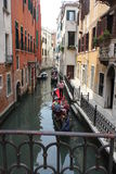 Gondolier της Βενετίας που επιπλέει σε ένα παραδοσιακό ενετικό κανάλι Στοκ Εικόνες