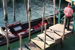 Gondolier стоя на пристани рядом с гондолой стоковая фотография