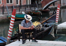 Gondolier. Venice,Italy,July 28th 2011: Portrait of a young gondolier using a mobile phone while waiting for clients near a venetian canal.Gondola is a major Royalty Free Stock Image