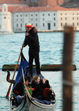Gondolier. Venice,Italy,February 25th 2011: Image of a gondolier propelling his gondola with tourists in front of the San Giorgio Maggiore Island in Venice Stock Image