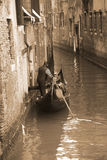 Gondolier carrying tourists in Venice, sepia tone Stock Photos