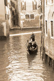 Gondolier carrying tourists in Venice, sepia tone Stock Photography