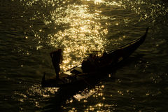 Gondolier et gondole dans le canal de Venise au coucher du soleil rétro-éclairé Photo libre de droits