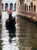 Gondolier ferrying tourists with its gondola in Venice Royalty Free Stock Photo