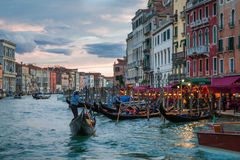 Gondolier floating near restaurants in Venice Stock Images