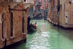 Gondolier floats on the narrow channel in Venice, Italy. Gondolier floats on the narrow channel Royalty Free Stock Photography