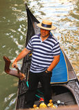 Gondolier in a gondola sailing on canal in Venice, Italy Stock Photography