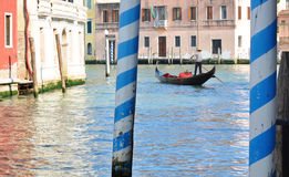 Gondolier and gondola in Venice. Gondolier rowing a gondola down a canal in Venice, Italy stock photography
