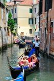 Gondolier navigating a gondola through canal. A shot of a gondolier navigation tourist through venice in a gondola Royalty Free Stock Photography