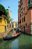 Gondolier navigating a gondola through canal Royalty Free Stock Photos