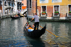 Gondolier navigating a gondola through canal. A shot of a gondolier navigation tourist through venice in a gondola Royalty Free Stock Photos