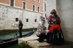 Masked couple in the Carnival of Venice. A gondolier passes by a masked couple during the traditional Carnival dresses and customs walk at fast pace in of Venice Stock Images