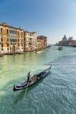 Gondolier pointing towards Basilica di Santa Maria in Venice Stock Photo