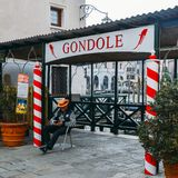 Gondolier reklamuje gondoli usługa relaksuje obok znaka z tradycyjnymi czerwonymi i białymi słupami obrazy stock