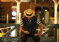 Gondolier resting at night in Venice, Italy Royalty Free Stock Photography
