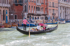 Gondolier rolls tourists on gondola on Grand Canal in Venice Royalty Free Stock Photos