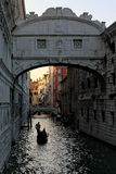 Gondolier rowing gondola in the canal before sunset in Venice, Italy. While gondolier rows gondolier to take a tourists watching the historic architecture Royalty Free Stock Photo