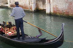 Gondolier rowing gondola in canal Stock Photography