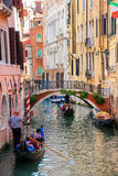 Gondolier rowing gondola with tourists on narrow canal in Venice Stock Photography