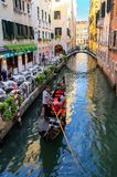 Gondolier rowing gondola with tourists on narrow canal in Venice Stock Photos
