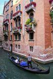Gondolier rowing gondola with tourists on narrow canal in Venice Stock Images