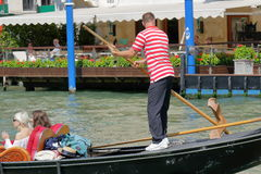 Gondolier rowing oar in gondola with passengers. Venice, Italy Stock Photo