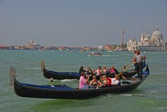 Gondolier rowing oar for tourist gondola in Venice gliding through the Venetian canal with them taking pictures & posing