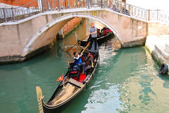 Gondolier sailing with tourists in a gondola along one of the ca Royalty Free Stock Photos