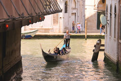 Gondolier sails with tourists sitting in a gondola down the narr Royalty Free Stock Photos