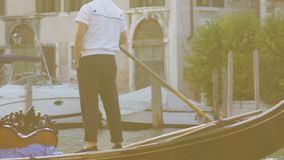 Gondolier standing at stern and rowing boat lazily, gesturing while having talk. Stock footage stock video footage