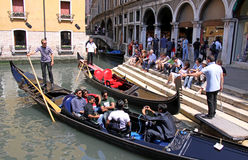 Gondolier and tourists in a gondola Royalty Free Stock Image