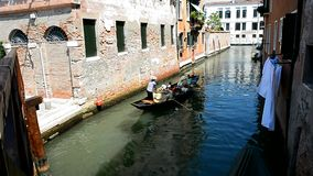 Gondolier is transporting tourists in a gondola stock footage