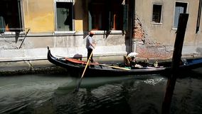 Gondolier is transporting tourists in a gondola on a narrow channel stock video