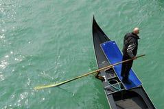 Gondolier on Venetian canal. Gondolier holding oar on gondola boat, Venetian canals, Venice, Veneto, Italy Royalty Free Stock Photo