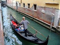 Gondolier in Venice. Gondola on narrow venetian canal Royalty Free Stock Image