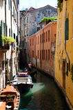 Gondolier in Venice - Italy. Little waterway in Venice with gondolier, houses,parking boats,entrances,windows, and roofgarden Royalty Free Stock Image