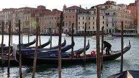 Gondoliere, der seine Gondel parkt und zu den Pfosten auf Grand Canal in Venedig ankoppelt stock video footage