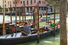 Gondoliere fotografiert die Touristen, die in einer Gondel, Venedig, Ita sitzen Lizenzfreies Stockfoto